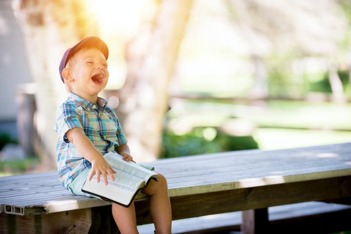 boy laughing on bench